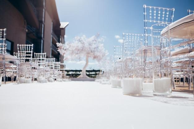 Transparente plastikstühle für die hochzeitszeremonie in einer reihe.