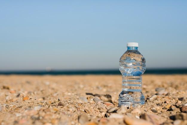 Transparente plastikwasserflasche im sand am strand