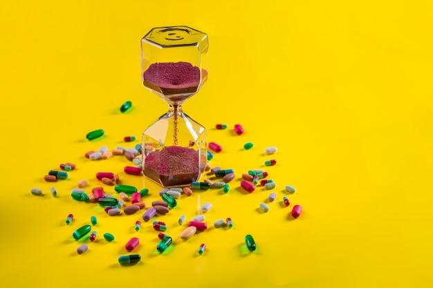 Transparente sanduhr der nahaufnahme mit roten sandkörnern in der mitte nahe bei liegenden tabletten