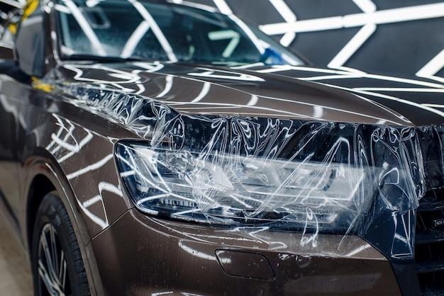 Transparente schutzfolie auf motorhaube, niemand. installation einer beschichtung, die den lack des automobils vor kratzern schützt. neues fahrzeug in der garage, tuning-verfahren