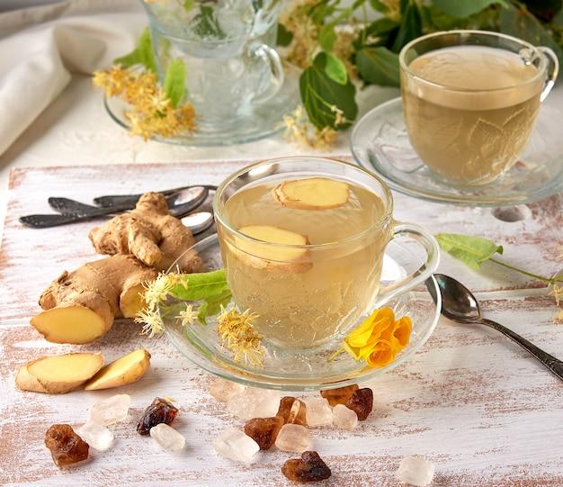 Transparente tasse kräuter-linden-tee und stücke ingwer