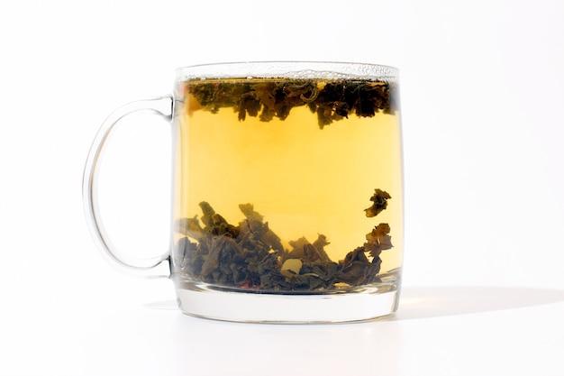Transparente tasse tee mit pudding auf weiß