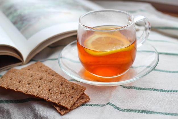 Transparente tasse tee mit zitrone, roggenknäckebrot, einem buch, tageslicht, frühstück