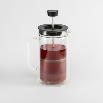 Transparente teekanne mit fruchtgetränk auf weißem hintergrund, getrennt. kolben teekanne