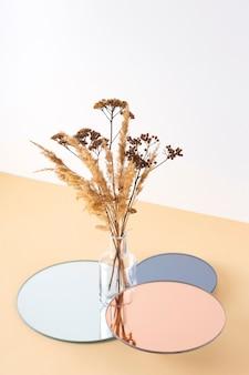 Transparente vase mit getrockneten blumen auf verspiegelten ständern