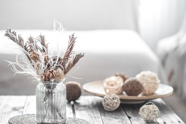 Transparente vase mit getrockneten blumen und teller mit fäden