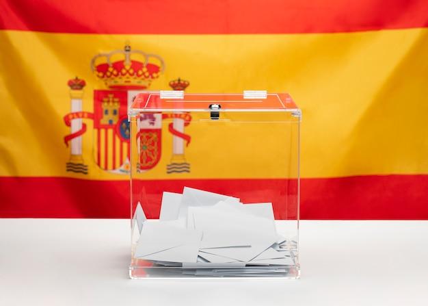 Transparente wahlurne auf spanischem flaggenhintergrund
