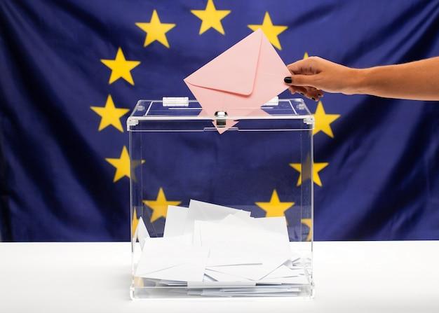 Transparente wahlurne gefüllt mit rosa umschlag und flagge der europäischen gemeinschaft