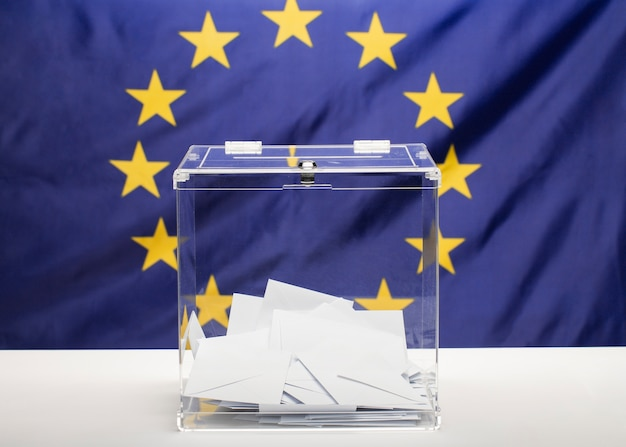 Transparente wahlurne gefüllt mit weißem umschlag und flagge der europäischen gemeinschaft