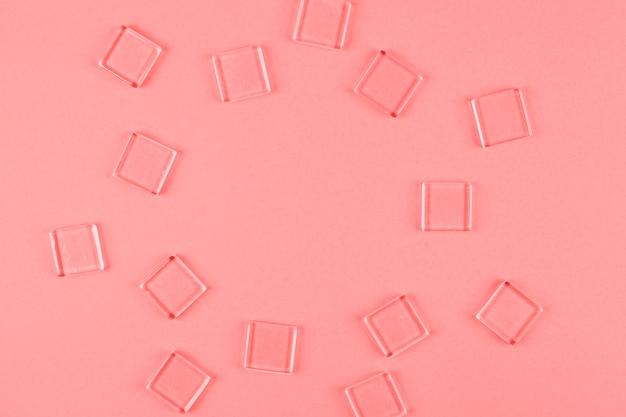 Transparente würfel in kreisform gegen korallenroten hintergrund angeordnet