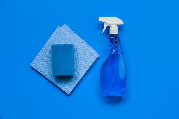 Transparenter blauer sprüher mit fensterputzer, lappen und schwamm auf blau