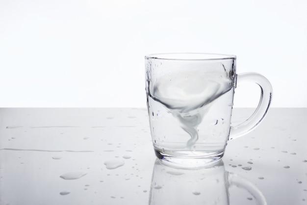 Transparenter glasbecher mit wasser auf leichter oberfläche mit wassertropfen. wasser in form eines tornados im becher, weichzeichner. ein sturm in einer teetasse