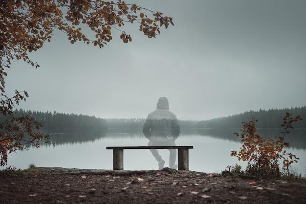 Transparenter mann sitzt auf einer bank und schaut auf den see. rückansicht. herbstthema