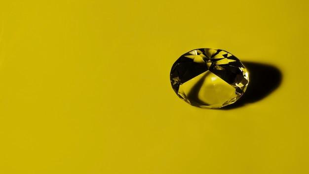 Transparenter runder diamant auf ockerhaltigem hintergrund