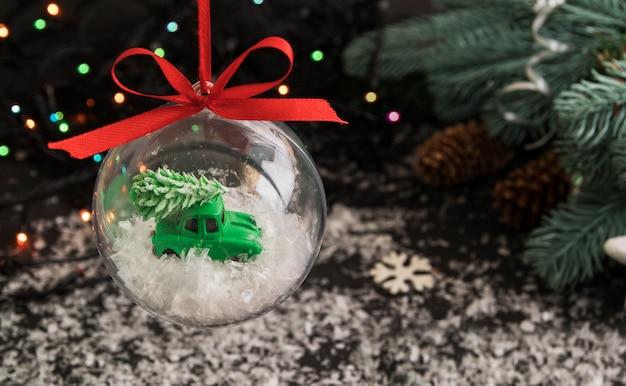 Transparenter weihnachtsball mit spielzeugauto und weihnachtsbaum mit schnee innen