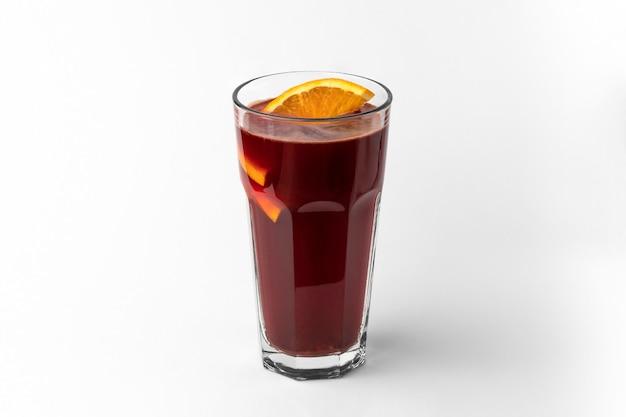 Transparentes glas dunkelroter erfrischender wintergetränk glühwein mit geschnittener orange einzeln auf weißem und grauem hintergrund mit natürlichem schatten