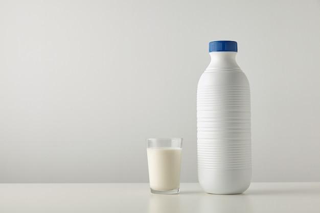 Transparentes glas mit frischer bio-milch in der nähe einer leeren plastikflasche mit blauem deckel, isoliert auf der seite des weißen tisches.