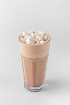 Transparentes glas mit raf-kaffee, dekoriert mit marshmallow aus espresso, milchschaum, sahne, sirup und topping einzeln auf weißem und grauem hintergrund mit natürlichem schatten