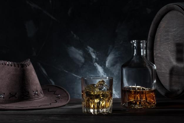 Transparentes glas mit whisky cowboyhut und karaffe