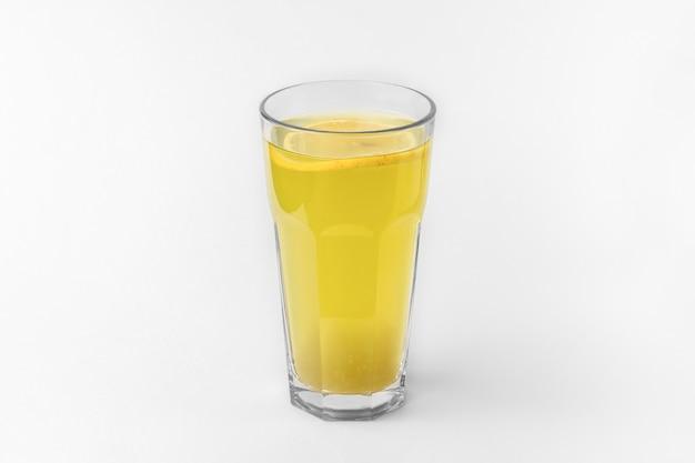 Transparentes glas pastellgrüner farbe, erfrischendes sommer- oder wintergetränk mit geschnittener orange einzeln auf weißem und grauem hintergrund mit natürlichem schatten
