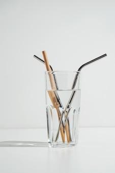 Transparentes glas wasser auf weiß mit nachhaltigen metall- und bambusstrohhalmen
