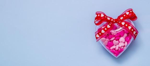 Transparentes herz mit perlen auf einem blauen hintergrund mit kopienraumfahne für valentinstag
