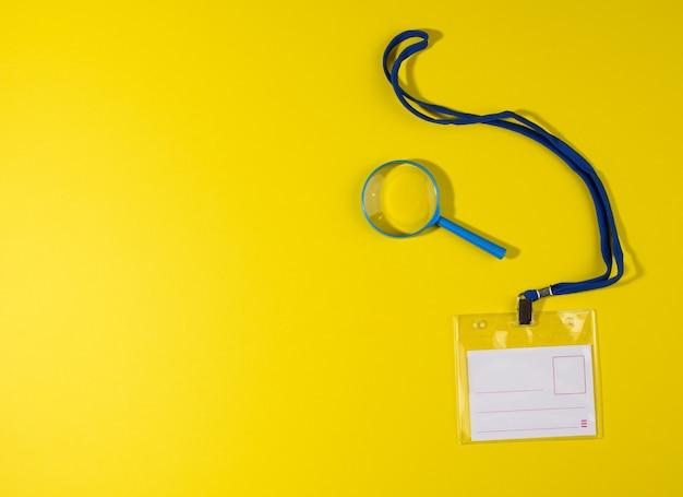 Transparentes plastikabzeichen auf blauem schlüsselband auf gelbem hintergrund, ansicht von oben