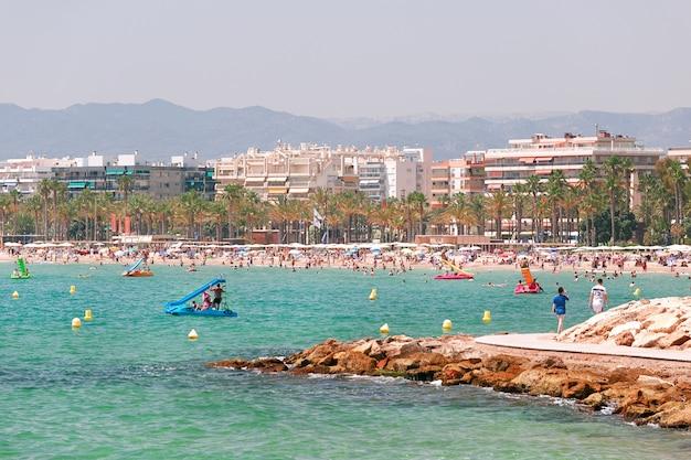 Transparentes und türkisfarbenes meer, strand mit touristen in salou, spanien.
