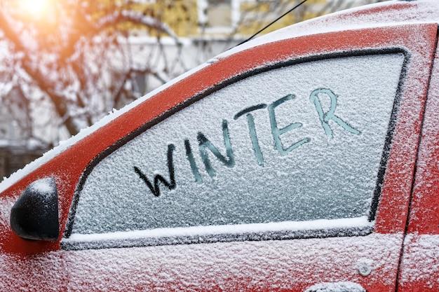 Transparentes wort winter geschrieben mit finger auf einem verschneiten seitenfenster eines autos, nahaufnahme