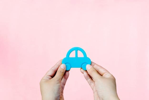 Transport, das auto in den händen auf einem rosa hintergrund