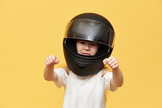 Transport-, extrem-, motorsport- und aktivitätskonzept. porträt des gefährlichen kleinen mädchenreiters im schwarzen schützenden motorradhelm, der hände vor ihr hält, als ob sie motorrad fahren