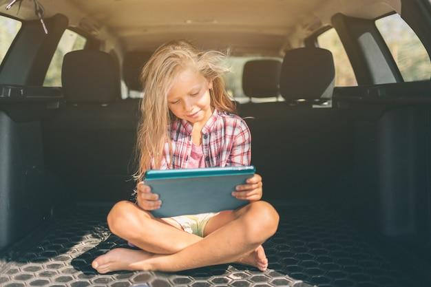 Transport-, roadtrip-, reise-, technologie- und personenkonzept - glückliches kleines mädchen mit tablet-pc
