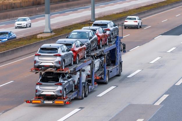 Transport von neuwagen auf einem anhänger mit einem lkw zur lieferung an händler.