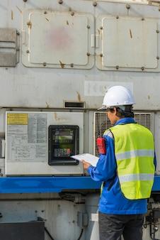 Transportingenieur, der die kühlcontainerbox in der logistikzone überprüft