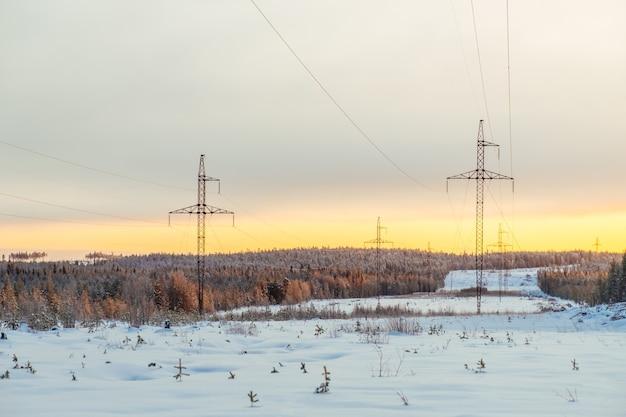 Transposition kraftübertragungstürme im verschneiten wald. hochspannungshalter