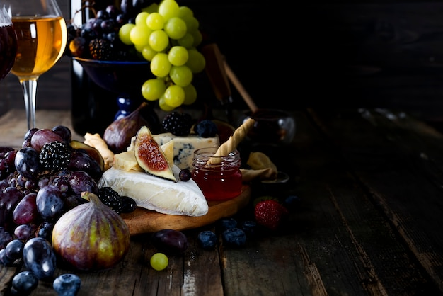Traube, käse, feigen und honig mit gläsern weißwein