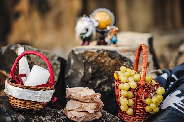 Trauben, äpfel, bananen, kerzen und geschenke werden bei einem picknick auf dem stein serviert