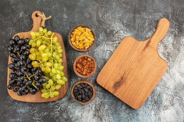 Trauben das schneidebrett bündel der leckeren trauben schalen mit getrockneten früchten