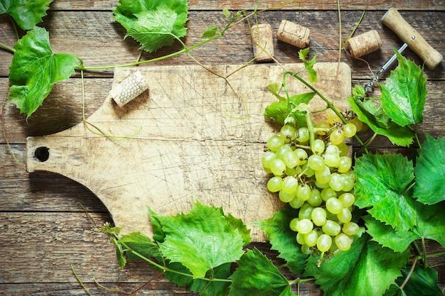 Trauben, eine flasche wein, korken und korkenzieher auf einer hölzernen alten tabelle, rustikale art