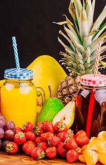 Trauben; erdbeeren; birnen; ananas- und saftflasche gegen schwarzen hintergrund