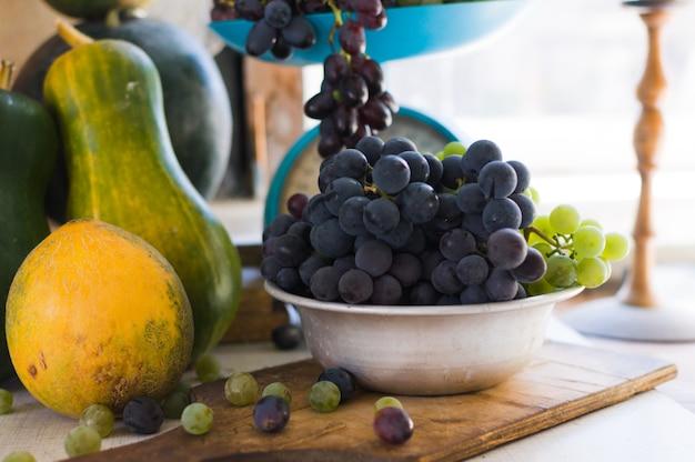 Trauben in einer metallschale, trauben sind auf einem weißen holztisch verstreut. herbsterntekonzept.