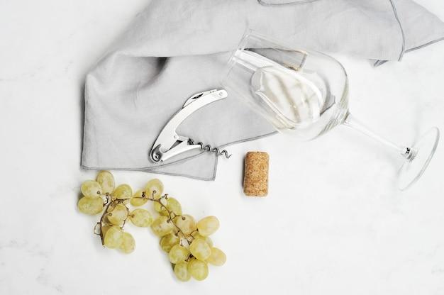 Trauben, korkenzieher, weinstopper und glas mit weißwein