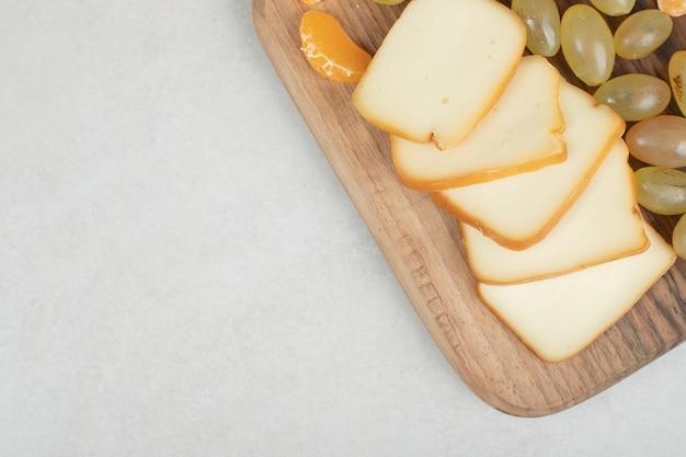 Trauben, mandarinen und käse auf holzbrett