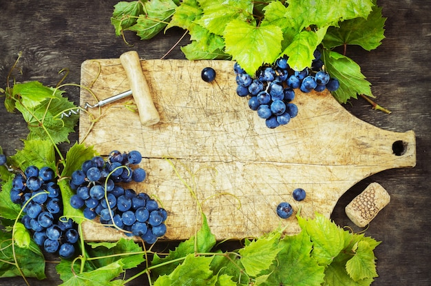 Trauben und altes brett auf einem hölzernen hintergrund