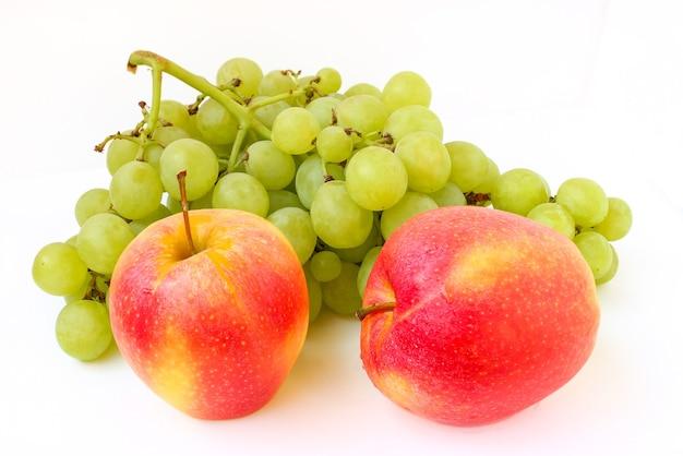 Trauben und ein apfel auf einem weißen