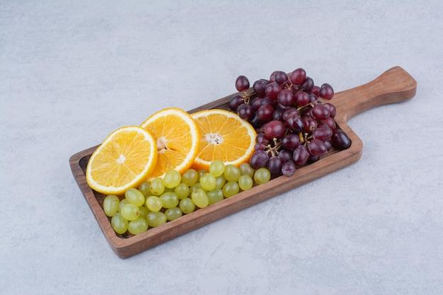Trauben und orangenscheiben auf holzbrett. foto in hoher qualität