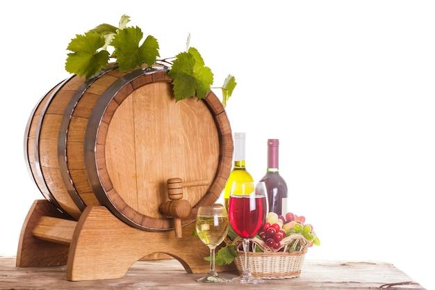 Trauben und weinflaschen in der nähe des holzfasses. weingläser auf dem tisch, konzept der weinkellerei - rot und weiß