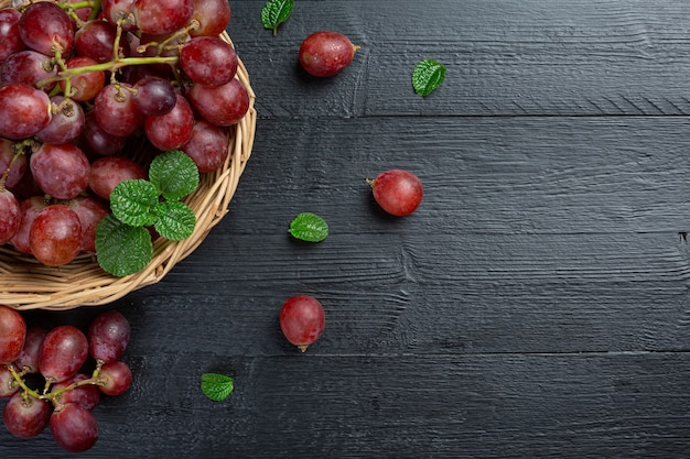 Trauben von frischen reifen roten trauben auf der dunklen holzoberfläche.