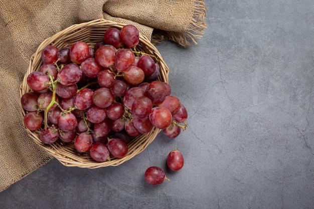 Trauben von frischen reifen roten trauben auf der dunklen oberfläche.
