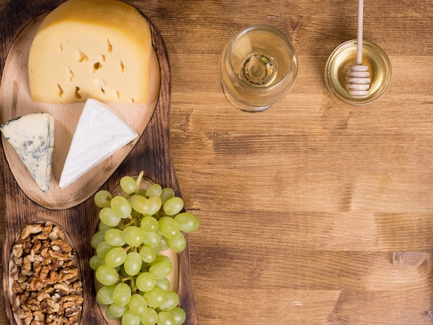 Trauben, weißwein. honig und nüsse über rustikalem holztisch. kopieren sie den verfügbaren speicherplatz. ansicht von oben.